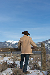 back of a cowboy looking out towards a mountain range