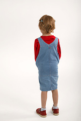Portrait of young girl standing with her back to the camera,