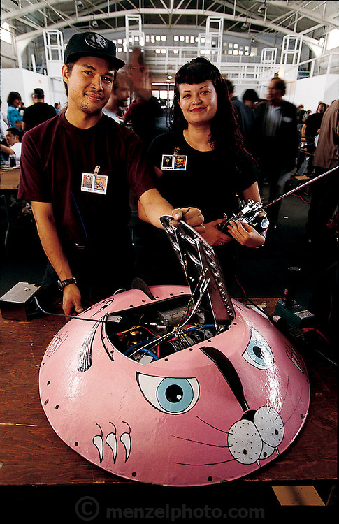 Painted pink to give competitors a false sense of its harmlessness, Mouser Catbot 2000 has two deadly sawblades in its nose and tail and a hidden flipper on its back for overturning enemy robots. Built by Californians Fon Davis and April Mousley (left to right), the machine deftly trounced Vlad the Impaler, a larger machine with a hydraulic spike that shot from its snout  at Robot Wars, a two-day festival of mechanical destruction at San Francisco's Fort Mason Center. California. From the book Robo sapiens: Evolution of a New Species, page 205.