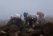 Chagga porters carry supplies up Mount Kilimanjaro, one of the world's largest volcanoes and the highest free-standing mountain, in Tanzania January 3, 2006. The mountain has become an icon for environmental campaigners, with scientists predicting that the mountain's glaciers will vanish within the next twenty years because of global warming. Some 20,000 tourists attempt to climb to the summit every year. REUTERS/Darrin Zammit Lupi