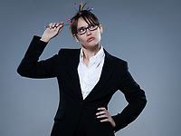 beautiful business woman looking at up holding  pencil on studio isolated grey bacground