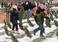 Goshen, New York - People carry wreaths to graves during a Wreaths Across America ceremony at Orange County Veterans Memorial Cemetery on Dec. 16, 2017. About 3,000 wreaths were placed at graves, and small American flags were added to the wreaths at veterans' graves.