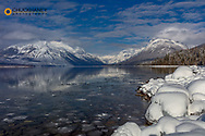 Mountains reflect in wintry Lake McDonald in Glacier National Park, Montana, USA
