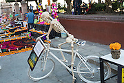 A skeleton on a bicycle in memory of cyclists that lost their lives in accidents during the Day of the Dead festival at the Jardin Principal in San Miguel de Allende, Guanajuato, Mexico. The week-long celebration is a time when Mexicans welcome the dead back to earth for a visit and celebrate life.