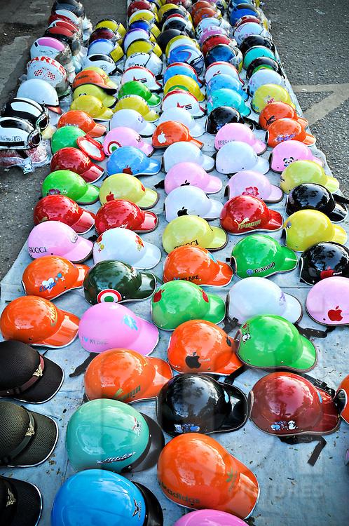 Multi-colored crash helmets are lined up on a Hue sidewalk, Vietnam, Southeast Asia