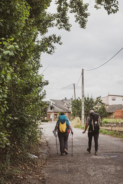 Pilgrims walking the Camino de Santiago pass through the sleepy town of Fuentes Nuevas, near Ponferrada, Spain. (July 2, 2018)