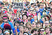 A festival attendee offers free shrugs in the crowd during The Bonnaroo Music and Arts Festival in Manchester, TN