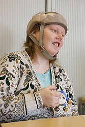 Drumming class for people with learning disabilities - woman with epilepsy wearing helmet