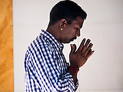 05 JUNE 2015 - KUALA LUMPUR, MALAYSIA:   A man prays in Sri Mahamariamman Temple, the oldest functioning and most important Hindu temple in Malaysia. The principal deity in the temple is Mariamman,  a deity that is popularly worshipped by overseas Indians, especially Tamils, because she is looked upon as their protector during the sojourn to foreign lands. Mariamman is a manifestation of the goddess Parvati, an incarnation embodying Mother Earth with all her terrifying force. She is associated with disease and fever and protects her devotees from unholy or demonic events.    PHOTO BY JACK KURTZ