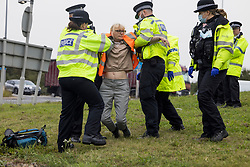 © Licensed to London News Pictures. 20/09/2021. Welwyn Garden City, UK. Scarborough councillor THERESA NORTON being arrested by police after attaching herself to the road. Protesters from Insulate Britain attempt to blockade the A1M junction 4 near Welwyn Garden City, Hertfordshire. Climate change activists Environmental protest group Insulate Britain have successfully blocked traffic at various points of the M25 on several occasions over the past week. Photo credit: Ben Cawthra/LNP