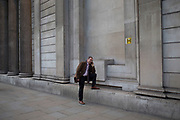 Man standing on a wall outside the Bank of England in the City of London, making a mobile phone call. UK.