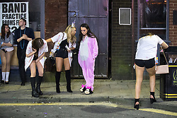 © Licensed to London News Pictures . 27/12/2016 . Wigan , UK . A woman vomits in to the gutter as another leans against a waste bin . Revellers in Wigan enjoy Boxing Day drinks and clubbing in Wigan Wallgate . In recent years a tradition has been established in which people go out wearing fancy-dress costumes on Boxing Day night . Photo credit : Joel Goodman/LNP