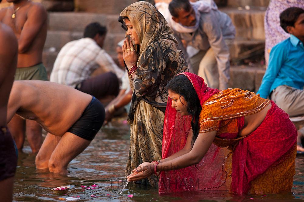 Indian Hindu pilgrim bathing and praying in The Ganges River at Dashashwamedh Ghat in Holy City of Varanasi, India
