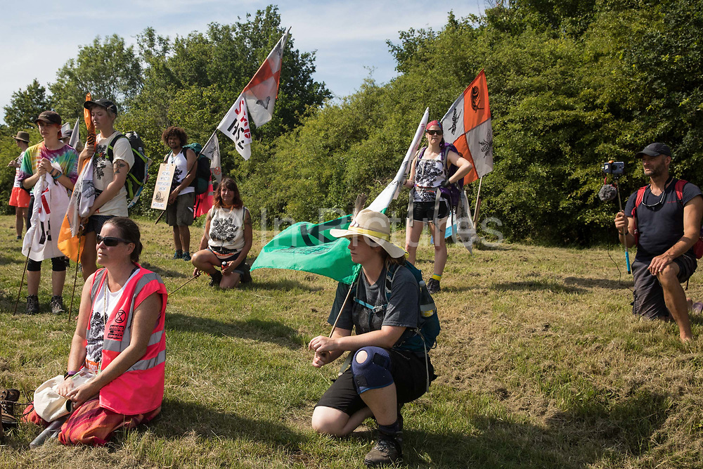 Activists from HS2 Rebellion and Extinction Rebellion UK take a knee for a recently felled mature oak tree during the 'Rebel Trail' hike along the route of the HS2 high-speed rail link on 26th June 2020 in Harefield, United Kingdom. The activists, who departed from Birmingham on 20th June and will arrive outside Parliament in London on 27th June, are protesting against the environmental impact of the high-speed rail link and questioning the viability of the £100bn+ project.