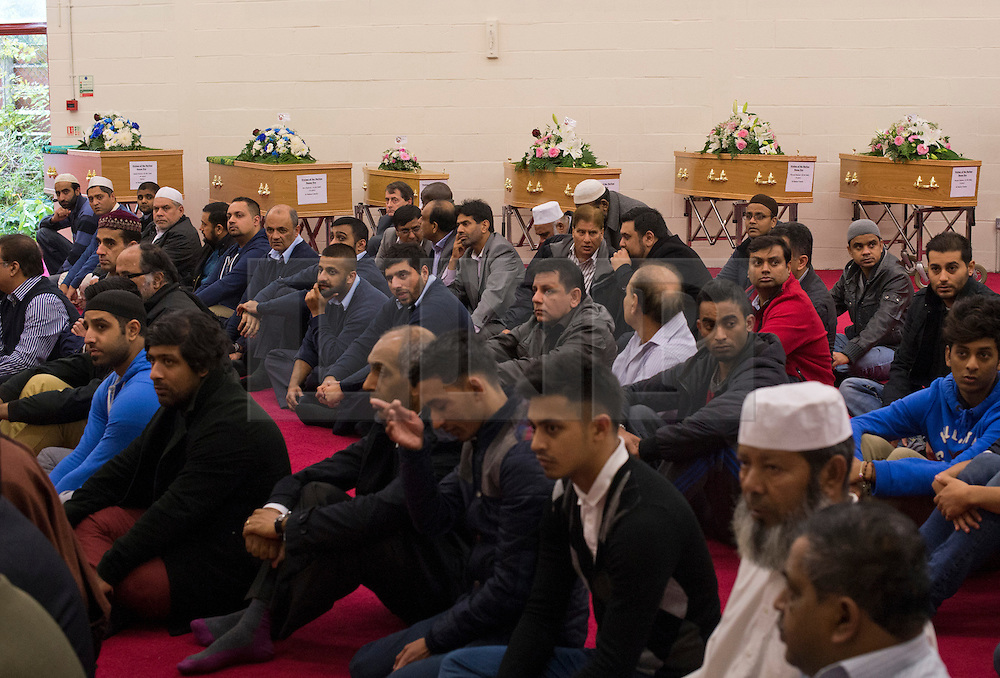 © London News Pictures. 24/10/2012. Harlow, UK. Members of the local Muslim community praying in front of the six coffins during the funeral service of Dr Sabah Usmani and her five children Hira (12), Sohaib (11) Muneeb (9), Rayyan (6) and Maheen (3) at Harlow Islamic Centre in Harlow, Essex, UK on October 24, 2012. Dr Sabah Usmani and her five children died blaze at their home in Harlow last week. Photo credit: Ben Cawthra/LNP