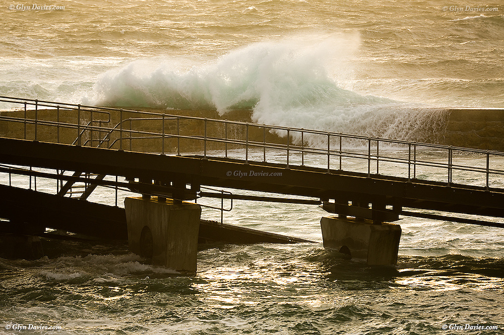 Powerful storm waves crash over Sennen breakwater at sunset, with the RNLI slipway in the foreground, South West Cornwall
