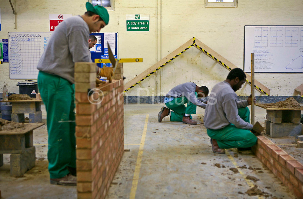 A prisoner on a building course builds a brick wall inside the building workshop at Wandsworth prison. HMP Wandsworth in South West London, United Kingdom, was built in 1851 and is one of the largest prisons in Western Europe. It has a capacity of 1456 prisoners.