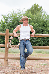 cowboy with a lasso leaning against a split rail fence