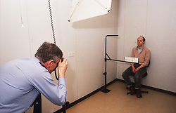 Suspect having his photo taken by police officer at police station,