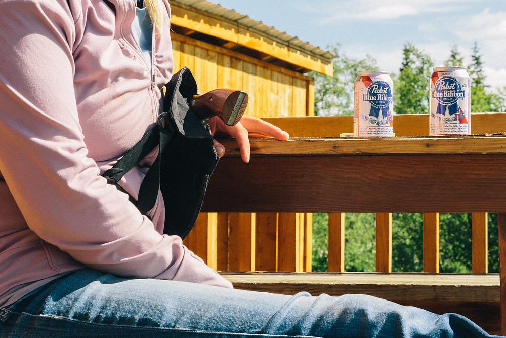 Anna Selanoff drinking PBR with her handgun sidearm at the Trout Lake Cabin near Cooper Landing, Alaska.