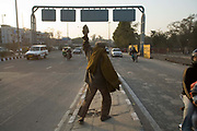 A homeless mentally ill man picks up a rock to throw at passing traffic. Delhi, India<br /> <br /> It is estimated that around than 150000 people - more than one percent of the city - is homeless and, with constant migration this is increasing on a daily basis. The incidence of mental illness amongst this group is very high. Delhi has little formal provision to deal with such a situation. Countrywide there are no more than 400 registered psychiatrists. Delhi, India
