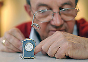 """©London News pictures...28/10/2010.  Michael Tooke changes the time on the smallest clock in the shop, a Swiss Guilloche Enamel from the early 1900's. . Staff at Horological Workshops start the task of changing the 100's of clocks at their store in Guildford, Surrey, UK. Micahel Tooke who has owned the store for 43 years and worked in the clock business all his life said. """"at this time of year we get alot of people who bring clocks in for repair after they have changed the time incorreectly by winding back the hands manually"""""""