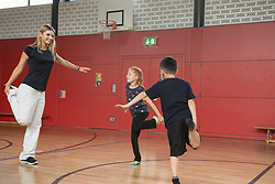 Teacher with children doing exercise in sports hall, Munich, Bavaria, Germany
