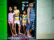 20 JANUARY 2018 - CAMALIG, ALBAY, PHILIPPINES: Children in the doorway of their dorm, which is actually a classroom, at the Barangay Cabangan evacuee shelter in a school in Camalig. There are about 650 people living at the shelter. They won't be allowed to move back to their homes until officials determine that Mayon volcano is safe and not likely to erupt. More than 30,000 people have been evacuated from communities on the near the Mayon volcano in Albay province in the Philippines. Most of the evacuees are staying at school in communities outside of the evacuation zone.   PHOTO BY JACK KURTZ