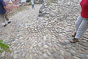 people walking down a steep cobble stoned path