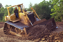 Stock photo of a bull dozer flattening out and leveling land at a construction site
