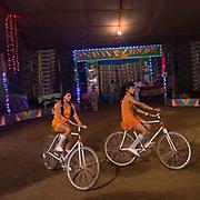 Girl cycling at a circus show.