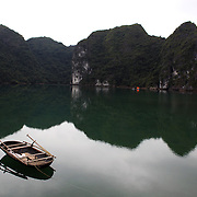 A tranquil scene of a moored boat on still waters on Cat Ba Island, the largest island in Ha Long Bay, Vietnam. The bay consists of a dense cluster of 1,969 limestone monolithic islands. Ha Long Bay, is a UNESCO World Heritage Site, and a popular tourist destination. Ha Long, Bay, Vietnam. 11th March 2012. Photo Tim Clayton
