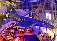 Garden City, New York, U.S.  November 14, 2019. At 17th Annual Cradle of Aviation Museum Air and Space Gala, CAM President ANDREW PARTON is speaking at podium at lower right, beneath real U.S. Navy Grumman F11 jet suspended from atrium ceiling, in Long Island.