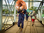 03 NOVEMBER 2015 - YANGON, MYANMAR: Stevedores carry cargo down to a boat on the Yangon docks.    PHOTO BY JACK KURTZ