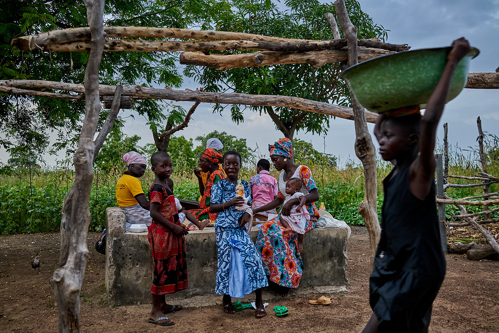 27/10/2019 / Kpatua / Ghana:<br /> Celebrants feast on a grave at the Christmas party in Joshua and Felicia's house in Kpatua.<br /> <br /> Oxfam built a solar powered pump in Kpatua to help over families become more resilient during dry seasons. Apart from community members coming to the pump twice a day, all year round, during the dry season, women use the water from the pump to farm vegetables for sale.