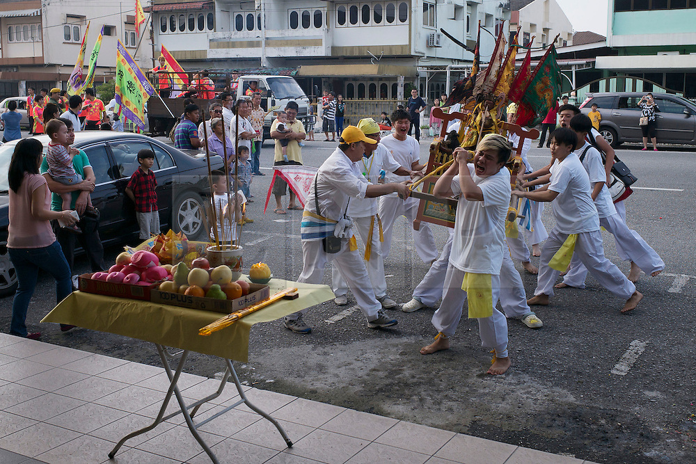 © Licensed to London News Pictures. 28/09/2014. Ipoh, Malaysia. Devotees carrying a deity pause at an offerings as they process through the streets of central Ipoh, Malaysia on the 5th day of the Nine Emperor Gods Festival, Sunday, Sept. 28, 2014. The festival is a nine-day Taoist celebration to mark the birth of the Nine Emperor Gods from the first day to the ninth day of the ninth moon in Chinese Lunar Calender. The origin of the Nine Emperor Gods (stars of the Northern constellation) can be traced back to the Taoist worship of the Northern constellation during Qin and Han Dynasty and absorb this practice of worshipping the stars and began to deitify them as Gods. Photo credit : Sang Tan/LNP