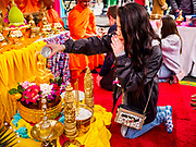"""29 APRIL 2017 - MINNEAPOLIS, MINNESOTA: A woman prays and bathes a statue of the Buddha at Songkran Uptown. Several thousand people attended Songkran Uptown on Hennepin Ave in Minneapolis for the city's first celebration of Songkran, the traditional Thai New Year. Events included a Thai parade, a performance of the Ramakien (the Thai version of the Indian Ramayana), a """"Ladyboy"""" (drag queen) show, and Thai street food.     PHOTO BY JACK KURTZ"""