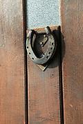 Close up of metal horse shoe door knocker in wooden front door, UK