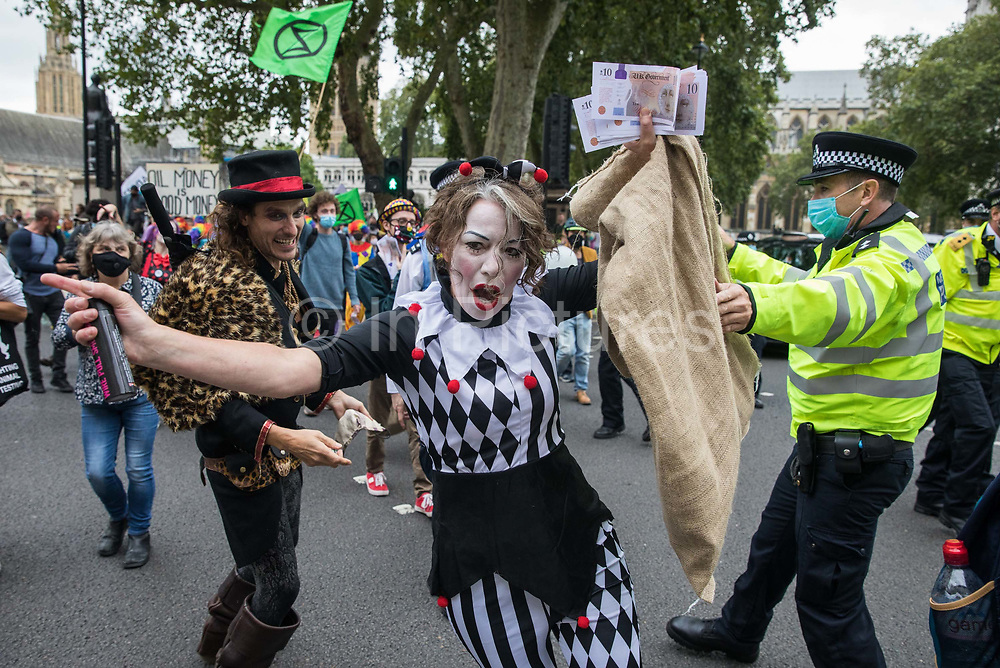 A troupe of clowns joins fellow climate activists from Extinction Rebellion attending a 'Carnival of Corruption' protest against the government's facilitation and funding of the fossil fuel industry on 3 September 2020 in London, United Kingdom. Extinction Rebellion activists are attending a series of September Rebellion protests around the UK to call on politicians to back the Climate and Ecological Emergency Bill CEE Bill which requires, among other measures, a serious plan to deal with the UK's share of emissions and to halt critical rises in global temperatures and for ordinary people to be involved in future environmental planning by means of a Citizens' Assembly.
