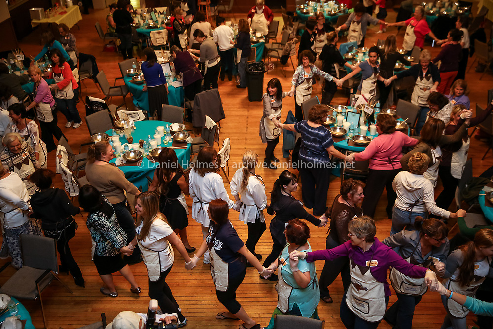 """(9/16/14, HOLLISTON, MA) Women dance during the Mega Challah Bake sponsored by the Chabad Jewish Community Center of Milford at Town Hall in Holliston on Tuesday. Rosh Hashanah, the Jewish New Year, begins Wednesday September 24 at sunset. When asked how the inaugural event came together, Rabbi Mendy Kivman said his wife Rochy Kivman """"had the idea to bring together as many jewish woman as possible to make challah."""" Approximately 150 women attended the Mega Challah Bake. Daily News and Wicked Local Photo/Dan Holmes"""