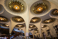 The Scala Cinema foyer is made up of a huge domed ceiling, ornately decorated with art deco bronzed flowers. The double circular staircases wind up to the second floor, passing under a huge white chandelier hanging from the ceiling.  Pillars from the ceiling descend down to the floor, creating a cathedral ambiance.  Traditionall ticket booths, right next to a wooden concession stand, are both art deco in design.  At the Scala Cinema, this old school style has been preserved, as everything else here has, since it's opening date.