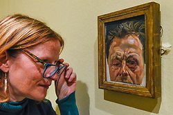 """© Licensed to London News Pictures. 23/10/2019. LONDON, UK. A staff member views """"Self-Portrait with a Black-Eye"""", 1978, by Lucien Freud. Preview of """"Lucian Freud: The Self-portraits"""" at the Royal Academy of Arts in Piccadilly.  56 works on display chart Freud's artistic development over almost seven decades on canvas and paper in a show which runs 27 October to 26 January 2020.  Photo credit: Stephen Chung/LNP"""