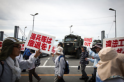 July 13, 2017 - Nago, Okinawa, Japan - Anti-US base protesters with their placards stage a rally in front of the Camp Schwab gate to protest against the construction of the new U.S Marine base in Henoko, Nago. Demonstrators chanted slogans against the plans and held placards decrying the US military presence as they lined the road leading to the marine base. (Credit Image: © Richard Atrero De Guzman/NurPhoto via ZUMA Press)