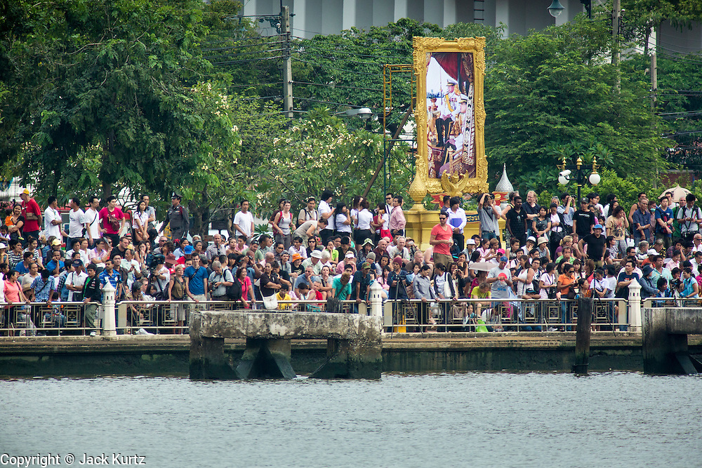 06 NOVEMBER 2012 - BANGKOK, THAILAND:  Members of the public gather underneath a portrait of Bhumibol Adulyadej, the King of Thailand, while they wait for the Royal Barge Procession rehearsal to begin. Thailand's Royal Barge Procession has both religious and royal significance. The tradition is nearly 700 years old. The Royal Barge Procession takes place rarely, typically coinciding with only the most important cultural and religious events. During the reign of King Bhumibol Adulyadej, spanning over 60 years, the Procession has only occurred 16 times. The Royal Barge Procession consists of 52 barges: 51 historical Barges, and the Royal Barge, the Narai Song Suban, which King Rama IX built in 1994. It is the only Barge built during King Bhumibol's reign. These barges are manned by 2,082 oarsmen. The Procession proceeds down the Chao Phraya River, from the Wasukri Royal Landing Place in Bangkok, passes the Grand Palace complex and ends at Wat Arun. Tuesday's dress rehearsal was the final practice for the 2012 Royal Barge Procession, which takes place November 9.    PHOTO BY JACK KURTZ