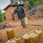 CAPTION: Damyano is seen here carrying water from a borehole pump to his home. Despite being extremely hearing impaired, blind in one eye and mute, he has married and now has two children, and indicates through sign language that he leads a happy life, largely thanks to the help of SignHealth Uganda. LOCATION: Kankamba Village, Lwengo District, Central Region, Uganda. INDIVIDUAL(S) PHOTOGRAPHED: .