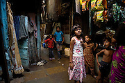 Rubina Ali, 9, the child actor playing the role of 'young Latika', the friend/lover of Jamal, protagonist of Slumdog Millionaire, the famous movie winner of 8 Oscar Academy Awards in December 2008, is portrayed next to a small local shop while on the streets near her uncle's house in the slum where she still lives with her family next to the train station of Bandra (East), Mumbai, India. Various promises were made to lift the two young actors (Azharuddin Ismail and Rubina Ali) from poverty and slum-life but as of the end of May 2009 anything is yet to happen. Rubina's house was recently demolished with no notice as it lay on land owned by the Maharashtra train authorities and she is now permanently living with her uncle's family in a home a stone-throw away in the same slum. Azharuddin's home too was demolished in the past two weeks, as it happens every year in his case, because the concrete walls were preventing local authorities to clear a drain passing right behind it. As usual, his father is looking into restoring the walls as soon as the work on the drain has been completed.