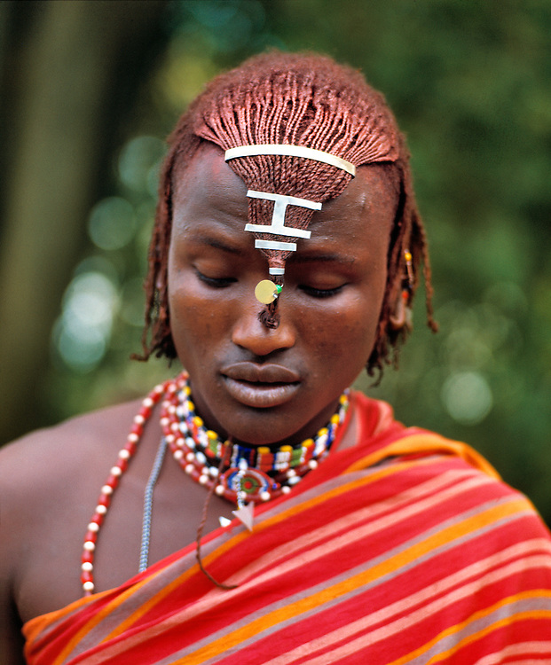 A young Masai warrior, or moran, visits with friends in Masai Mara National Reserve in Kenya.