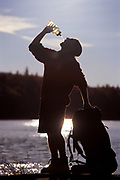 Hiker stops by a lake to take a drink.
