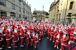 © Licensed to London News Pictures. 15/12/2013. Oxford, UK. Thousands of people take part in a Santa ran around the picturesque streets of Oxford this morning, to raise money for the charity Helen and Douglas House Hospice. Photo credit: MarknHemsworth/LNP