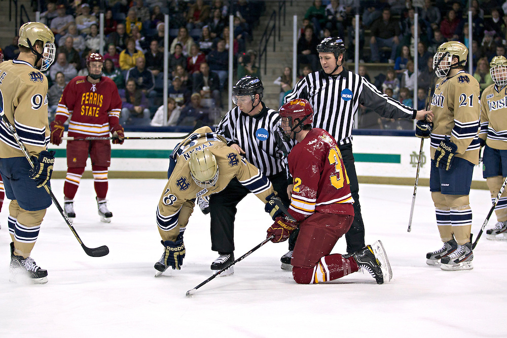 The linesmen separate Ferris State defenseman Tommy Hill (#32) and Notre Dame center T.J. Tynan (#18) in second period action during NCAA hockey game between Notre Dame and Ferris State.  The Notre Dame Fighting Irish defeated the Ferris State Bulldogs 4-1 in game at the Compton Family Ice Arena in South Bend, Indiana.